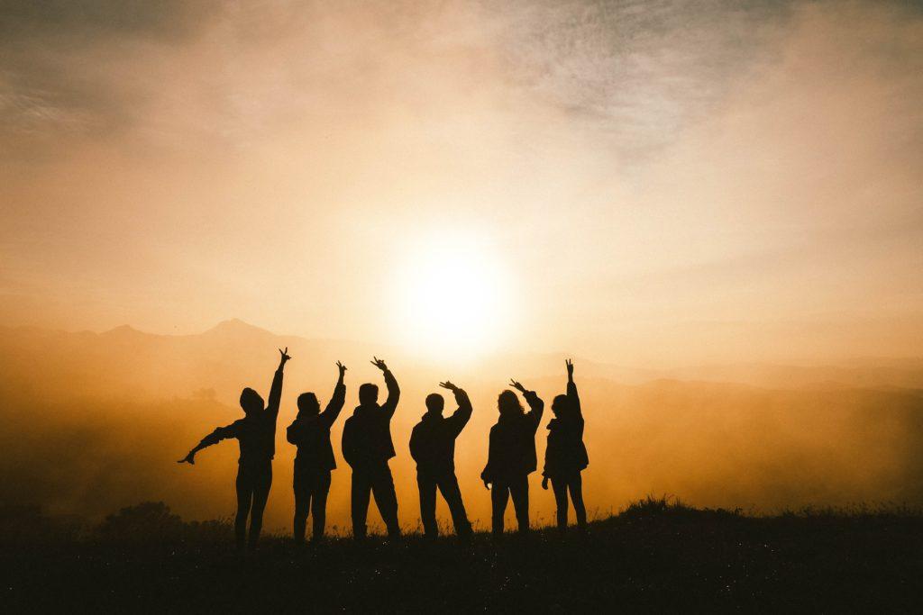 Jugendliche in Silhuette vor dem Sonnenuntergang zeigen das Peace-Zeichen