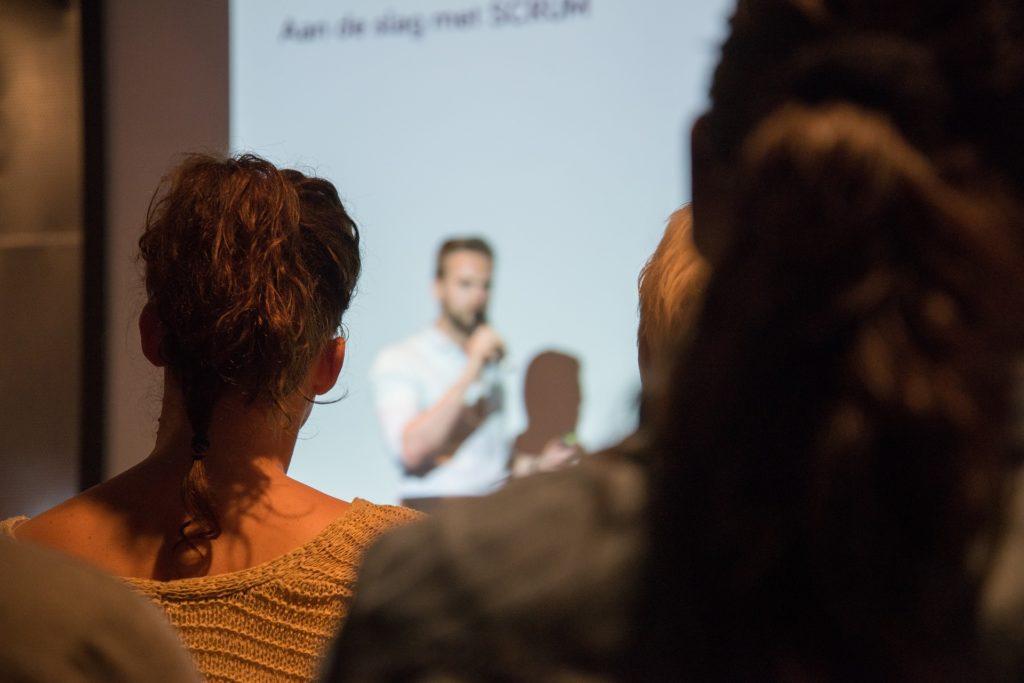Präsentation mit Mikrofon vor Leinwand