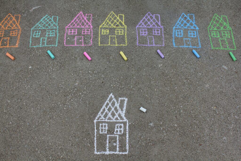 Bunte Häuser mit Kreide auf dem Boden gemalt.