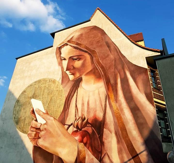 Maria mit einem Smartphone als Grafitty auf einer Hauswand.