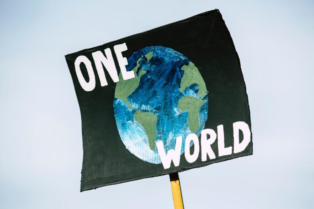"""Protest-Schild mit der Aufschrift """"One World"""""""